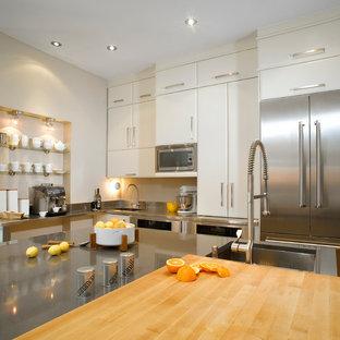 Неиссякаемый источник вдохновения для домашнего уюта: большая угловая кухня в стиле модернизм с техникой из нержавеющей стали, обеденным столом, врезной раковиной, плоскими фасадами, белыми фасадами, столешницей из кварцевого агломерата, фартуком цвета металлик, фартуком из металлической плитки, светлым паркетным полом и островом