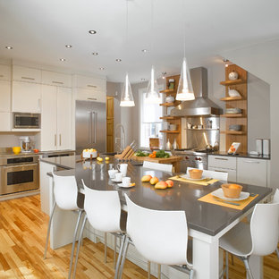 Eat-in kitchen - large contemporary l-shaped light wood floor eat-in kitchen idea in Montreal with stainless steel appliances, an undermount sink, flat-panel cabinets, white cabinets, quartz countertops, metallic backsplash, metal backsplash and an island