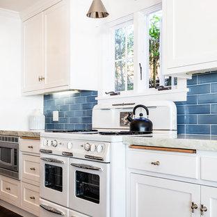 Large beach style kitchen appliance - Large coastal dark wood floor and brown floor kitchen photo in Sacramento with shaker cabinets, white cabinets, granite countertops, blue backsplash, ceramic backsplash, gray countertops and white appliances