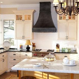 На фото: кухня в классическом стиле с фасадами с утопленной филенкой, бежевыми фасадами, белым фартуком и фартуком из плитки кабанчик с