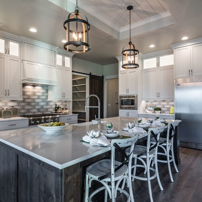 Farmhouse l-shaped dark wood floor and brown floor kitchen photo in Boise with a farmhouse sink, shaker cabinets, white cabinets, gray backsplash, stainless steel appliances, an island and white countertops