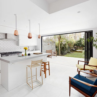 Photo of a contemporary kitchen in London with flat-panel cabinets, white cabinets, white splashback, metro tiled splashback, an island and white floors.