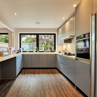 This is an example of a contemporary u-shaped kitchen in Essex with flat-panel cabinets, grey cabinets, beige splashback, stainless steel appliances, dark hardwood flooring, a breakfast bar, brown floors and beige worktops.