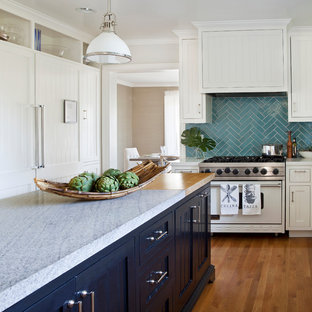 Photo of a mid-sized traditional l-shaped kitchen in Los Angeles with beaded inset cabinets, white cabinets, marble benchtops, blue splashback, cement tile splashback, white appliances, medium hardwood floors and with island.