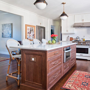 Transitional eat-in kitchen ideas - Transitional l-shaped medium tone wood floor and brown floor eat-in kitchen photo in Nashville with shaker cabinets, medium tone wood cabinets, white backsplash, stainless steel appliances and an island