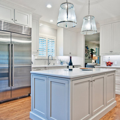 Example of a mid-sized transitional l-shaped medium tone wood floor and brown floor eat-in kitchen design in Nashville with an undermount sink, recessed-panel cabinets, white cabinets, quartz countertops, white backsplash, subway tile backsplash, stainless steel appliances, an island and white countertops