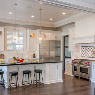 Traditional enclosed kitchen inspiration - Example of a classic l-shaped dark wood floor enclosed kitchen design in Los Angeles with shaker cabinets, white cabinets, white backsplash, stainless steel appliances and an island