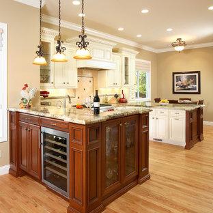 Bild på ett mellanstort vintage u-kök, med granitbänkskiva, en undermonterad diskho, luckor med infälld panel, beige stänkskydd, rostfria vitvaror, ljust trägolv, skåp i mellenmörkt trä, en halv köksö och stänkskydd i kalk