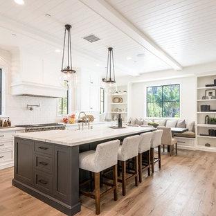 Klassische Wohnküche in L-Form mit Schrankfronten im Shaker-Stil, weißen Schränken, Küchenrückwand in Weiß, Rückwand aus Metrofliesen, Küchengeräten aus Edelstahl, braunem Holzboden, Kücheninsel, braunem Boden und weißer Arbeitsplatte in Los Angeles