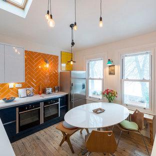 ロンドンの中くらいのエクレクティックスタイルのおしゃれなキッチン (アンダーカウンターシンク、フラットパネル扉のキャビネット、黒いキャビネット、オレンジのキッチンパネル、サブウェイタイルのキッチンパネル、シルバーの調理設備、無垢フローリング、アイランドなし、茶色い床、白いキッチンカウンター) の写真