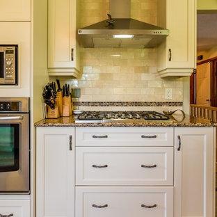 トロントの中サイズのトランジショナルスタイルのおしゃれなキッチン (シングルシンク、落し込みパネル扉のキャビネット、ベージュのキャビネット、クオーツストーンカウンター、ベージュキッチンパネル、サブウェイタイルのキッチンパネル、シルバーの調理設備の、磁器タイルの床) の写真