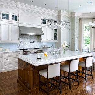 Elegant eat-in kitchen photo in Toronto with recessed-panel cabinets, white cabinets and glass sheet backsplash