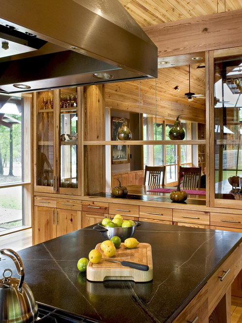 Country kitchen photo in Charleston with glass-front cabinets, soapstone  countertops and medium tone