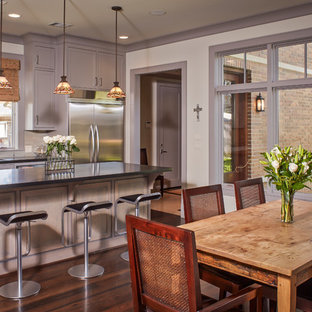 Large traditional eat-in kitchen pictures - Example of a large classic dark wood floor eat-in kitchen design in Houston with recessed-panel cabinets, gray cabinets, beige backsplash, stainless steel appliances, an island and a double-bowl sink