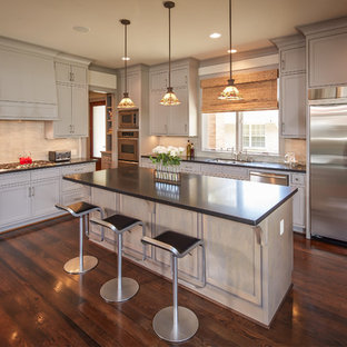 Large traditional eat-in kitchen inspiration - Eat-in kitchen - large traditional l-shaped dark wood floor eat-in kitchen idea in Houston with recessed-panel cabinets, gray cabinets, beige backsplash, stainless steel appliances, a double-bowl sink and an island