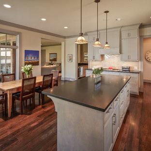Large traditional eat-in kitchen ideas - Inspiration for a large timeless dark wood floor eat-in kitchen remodel in Houston with recessed-panel cabinets, gray cabinets, beige backsplash, stainless steel appliances, a double-bowl sink and an island