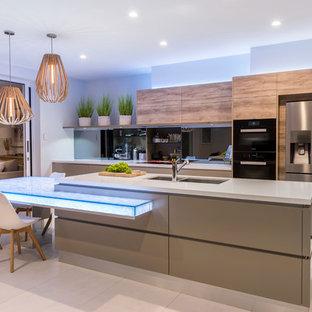 ブリスベンの中サイズのコンテンポラリースタイルのおしゃれなキッチン (ダブルシンク、フラットパネル扉のキャビネット、ガラスカウンター、ミラータイルのキッチンパネル、ベージュの床、中間色木目調キャビネット、黒い調理設備、グレーのキッチンカウンター) の写真