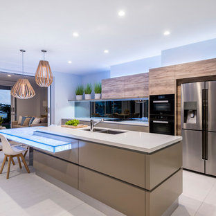 Large contemporary galley open plan kitchen in Brisbane with a double-bowl sink, flat-panel cabinets, cement tiles, with island, beige floor, beige benchtop, medium wood cabinets, black splashback and stainless steel appliances.