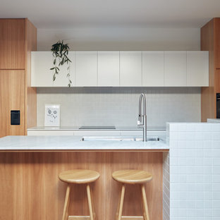 This is an example of a scandinavian kitchen in Melbourne with an undermount sink, flat-panel cabinets, white cabinets, white splashback, light hardwood floors and white benchtop.