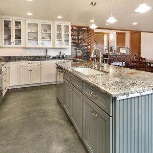 Immagine di una cucina ad U costiera con lavello sottopiano, ante di vetro, ante bianche, top in granito, paraspruzzi grigio, paraspruzzi in lastra di pietra, elettrodomestici in acciaio inossidabile, pavimento in cemento, penisola, pavimento verde e top grigio