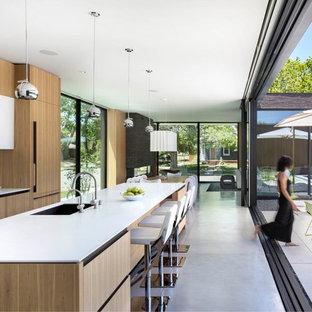 Idee per una cucina moderna con lavello sottopiano, ante lisce, ante in legno chiaro, paraspruzzi bianco, elettrodomestici da incasso, pavimento in cemento, isola, pavimento grigio e top bianco