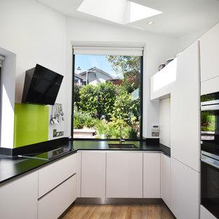 Mittelgroße Moderne Küche ohne Insel in U-Form mit flächenbündigen Schrankfronten, weißen Schränken, Quarzwerkstein-Arbeitsplatte, Vinylboden, schwarzer Arbeitsplatte, Waschbecken und Küchenrückwand in Grün in Cork