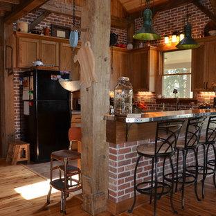 インディアナポリスの中サイズのカントリー風おしゃれなキッチン (アンダーカウンターシンク、シェーカースタイル扉のキャビネット、茶色いキャビネット、人工大理石カウンター、赤いキッチンパネル、テラコッタタイルのキッチンパネル、シルバーの調理設備、セラミックタイルの床) の写真