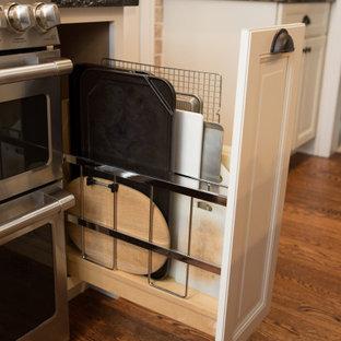 シカゴの中くらいのトランジショナルスタイルのおしゃれなキッチン (エプロンフロントシンク、落し込みパネル扉のキャビネット、淡色木目調キャビネット、御影石カウンター、ベージュキッチンパネル、レンガのキッチンパネル、シルバーの調理設備、無垢フローリング、茶色い床、マルチカラーのキッチンカウンター) の写真