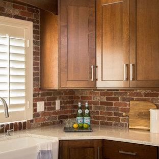 デンバーの広いラスティックスタイルのおしゃれなキッチン (エプロンフロントシンク、シェーカースタイル扉のキャビネット、濃色木目調キャビネット、クオーツストーンカウンター、赤いキッチンパネル、テラコッタタイルのキッチンパネル、シルバーの調理設備、濃色無垢フローリング) の写真