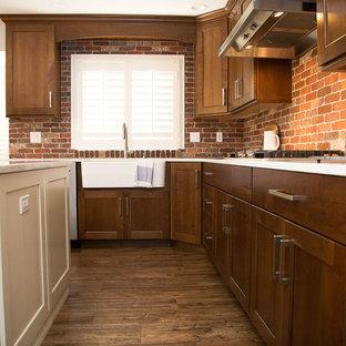 デンバーの広いカントリー風おしゃれなキッチン (エプロンフロントシンク、シェーカースタイル扉のキャビネット、濃色木目調キャビネット、クオーツストーンカウンター、赤いキッチンパネル、シルバーの調理設備、濃色無垢フローリング) の写真