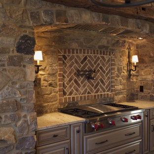 Traditional eat-in kitchen ideas - Example of a classic medium tone wood floor eat-in kitchen design in Other with a farmhouse sink, raised-panel cabinets, medium tone wood cabinets, granite countertops, brown backsplash, stone tile backsplash, stainless steel appliances and two islands
