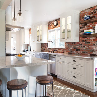Mid-sized farmhouse eat-in kitchen designs - Example of a mid-sized cottage galley medium tone wood floor and brown floor eat-in kitchen design in Sacramento with a farmhouse sink, recessed-panel cabinets, white cabinets, quartzite countertops, red backsplash, stone tile backsplash, stainless steel appliances and an island