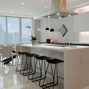 This is an example of a large modern l-shaped eat-in kitchen in Miami with an undermount sink, glass-front cabinets, grey cabinets, quartzite benchtops, white splashback, slate splashback, stainless steel appliances, marble floors, with island and white floor.