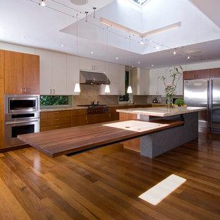 Moderne Küche mit Küchengeräten aus Edelstahl, Arbeitsplatte aus Holz, flächenbündigen Schrankfronten und hellbraunen Holzschränken in Toronto