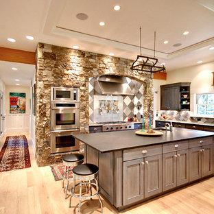 他の地域の広いトランジショナルスタイルのおしゃれなキッチン (アンダーカウンターシンク、亜鉛製カウンター、グレーのキッチンパネル、シルバーの調理設備、淡色無垢フローリング、落し込みパネル扉のキャビネット、グレーのキャビネット、茶色い床) の写真