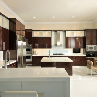 Large contemporary open concept kitchen appliance - Inspiration for a large contemporary u-shaped ceramic floor and white floor open concept kitchen remodel in Miami with flat-panel cabinets, dark wood cabinets, white backsplash, glass sheet backsplash, stainless steel appliances, an island, an undermount sink and solid surface countertops