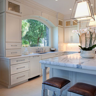 Photo of a mid-sized traditional l-shaped eat-in kitchen in Charleston with an undermount sink, recessed-panel cabinets, white cabinets, white splashback, stone tile splashback, stainless steel appliances, ceramic floors and with island.