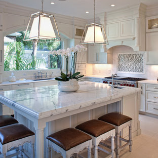 Mid-sized traditional eat-in kitchen designs - Example of a mid-sized classic l-shaped ceramic floor eat-in kitchen design in Charleston with an undermount sink, recessed-panel cabinets, white cabinets, white backsplash, stainless steel appliances and an island