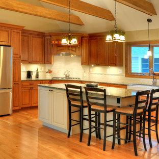 Idéer för ett stort, avskilt amerikanskt grå l-kök, med en rustik diskho, skåp i mellenmörkt trä, bänkskiva i kvartsit, vitt stänkskydd, stänkskydd i tunnelbanekakel, rostfria vitvaror, ljust trägolv, en köksö, luckor med upphöjd panel och brunt golv