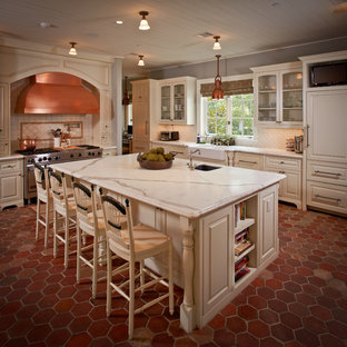 Photo of a traditional kitchen in Houston with a farmhouse sink, glass-front cabinets, beige cabinets, white splashback, subway tile splashback and panelled appliances.