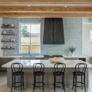 Inspiration for a transitional kitchen in Austin with a farmhouse sink, open cabinets, multi-coloured splashback, stainless steel appliances, concrete floors and with island.