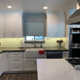 Photo of a mid-sized contemporary l-shaped eat-in kitchen in Sacramento with a farmhouse sink, shaker cabinets, white cabinets, quartz benchtops, white splashback, ceramic splashback, stainless steel appliances, vinyl floors, with island, brown floor and white benchtop.