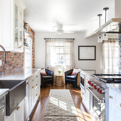 Example of a mid-sized farmhouse galley medium tone wood floor and brown floor eat-in kitchen design in Sacramento with a farmhouse sink, shaker cabinets, white cabinets, quartzite countertops, blue backsplash, ceramic backsplash, stainless steel appliances and an island