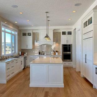 Photo of a transitional u-shaped kitchen in Edmonton with an undermount sink, shaker cabinets, white cabinets, quartz benchtops, beige splashback, brick splashback, stainless steel appliances, plywood floors, with island, purple floor and beige benchtop.