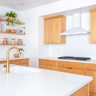 Inspiration for a mid-sized midcentury u-shaped eat-in kitchen in Phoenix with an undermount sink, flat-panel cabinets, light wood cabinets, quartz benchtops, white splashback, stainless steel appliances, light hardwood floors, with island, brown floor and white benchtop.