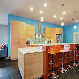 Large contemporary galley open plan kitchen in Tampa with flat-panel cabinets, red cabinets, recycled glass benchtops, blue splashback, glass tile splashback, stainless steel appliances, porcelain floors and with island.