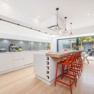 This is an example of a contemporary galley kitchen/diner in Other with flat-panel cabinets, white cabinets, wood worktops, grey splashback, black appliances, light hardwood flooring, an island and beige floors.