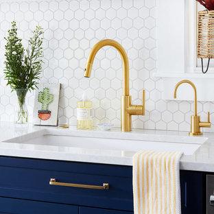 Inredning av ett modernt vit vitt kök, med en enkel diskho, skåp i shakerstil, blå skåp, bänkskiva i kvarts, vitt stänkskydd, stänkskydd i keramik, rostfria vitvaror, skiffergolv och grönt golv