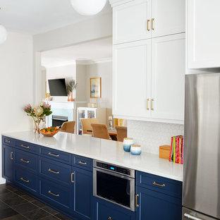 Foto di una cucina contemporanea con lavello a vasca singola, ante in stile shaker, ante blu, top in quarzo composito, paraspruzzi bianco, paraspruzzi con piastrelle in ceramica, elettrodomestici in acciaio inossidabile, pavimento in ardesia, nessuna isola, pavimento verde e top bianco