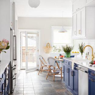 シカゴのビーチスタイルのおしゃれなキッチン (シェーカースタイル扉のキャビネット、青いキャビネット、クオーツストーンカウンター、白いキッチンパネル、セラミックタイルのキッチンパネル、シルバーの調理設備の、スレートの床、アイランドなし、白いキッチンカウンター、アンダーカウンターシンク、茶色い床) の写真